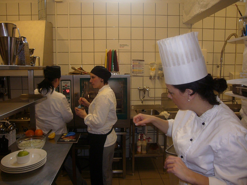 This picture shows women working in a prison's kitchen while learning basic skills. Here the focus is on mathematics and oral skills.