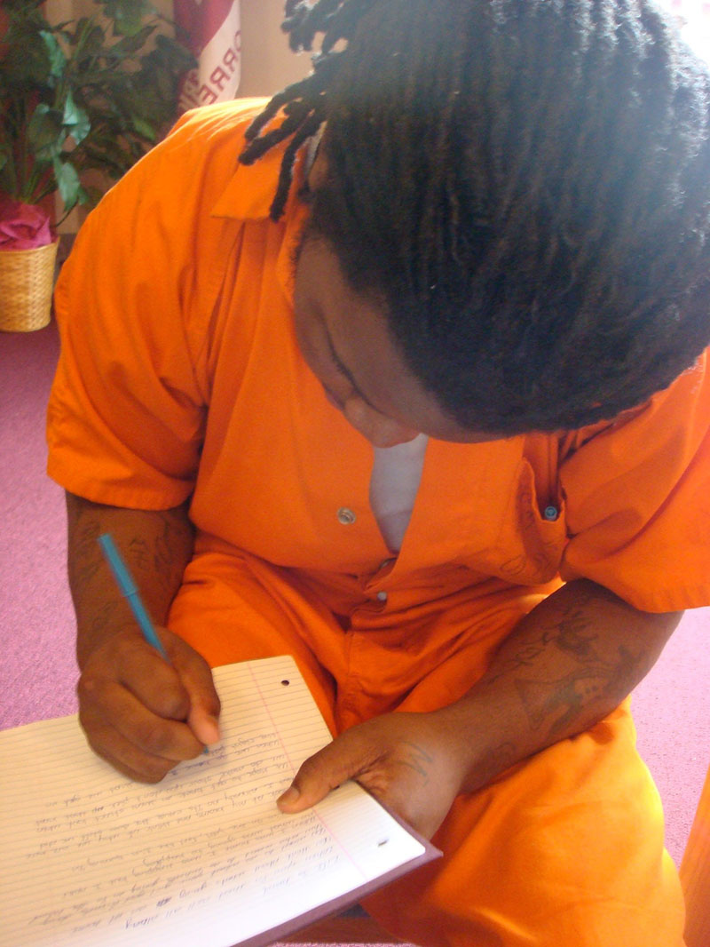 A teenager writing in the Book Club at the DC Jail